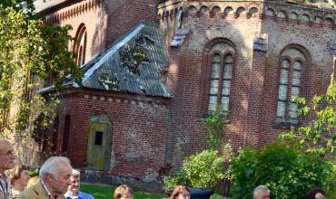 Plaškių bažnyčia – tarsi gyvas priekaištas jos niokotojams. Jos paradinės durys nebuvo pravertos. Tačiau būtent prie šios bažnyčios durų prasidėjo iškilmės, nes į praeitį atsigręžusiam Plaškių kaimui ji – sudėtingą istoriją turinčio kaimo simbolis. B. Bagdonas konferencijoje priminė, kad  sovietmečiu nuo bažnyčios buvo nuimtos aliuminuotos čerpės, kuriomis namą apsidengė vienas šilutiškis...  Šventoriuje – seni kapai, ant kurių buvo padėta uždegtų žvakelių: pagerbti amžinojo poilsio atgulusieji.