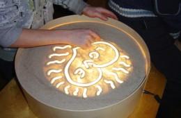 Piešiant ant šviesos staliukų naudojamos įvairios medžiagos: smėlis, manų kruopos, kukurūzų miltai, grikiai, žirniai...