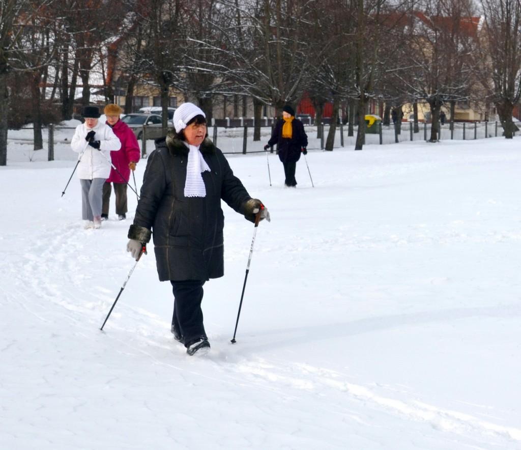 Trečiadienį būrelis senjorių su šiaurietiško ėjimo lazdomis mankštinosi apsnigtame stadione Šilutėje.