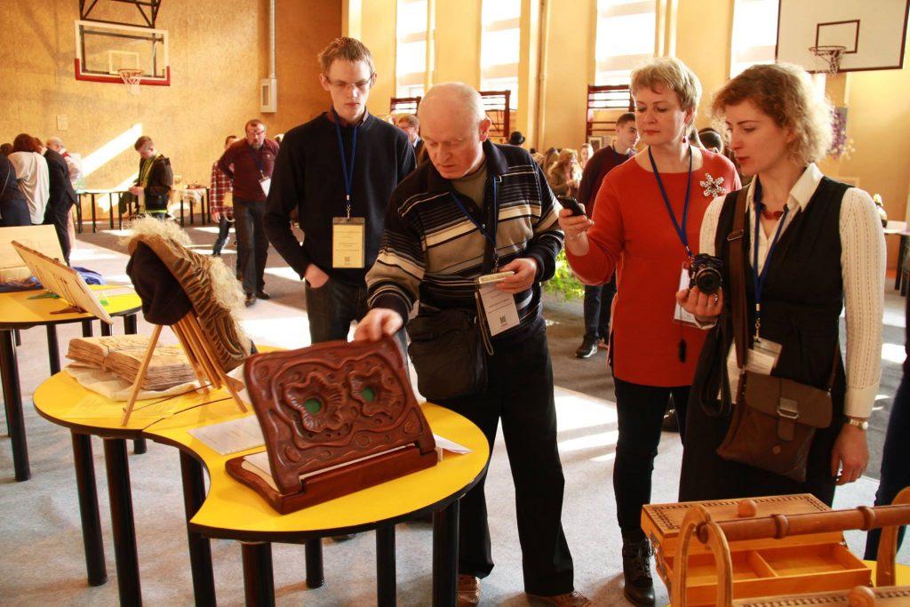 A. H. Tumaitis (kairėje) ir jo mokytojas E. Naujokas technologijos olimpiados lankytojoms rodo medinę knygą, papuoštą reljefinėmis figūromis, ir aiškina subtilų jos gamybos procesą.