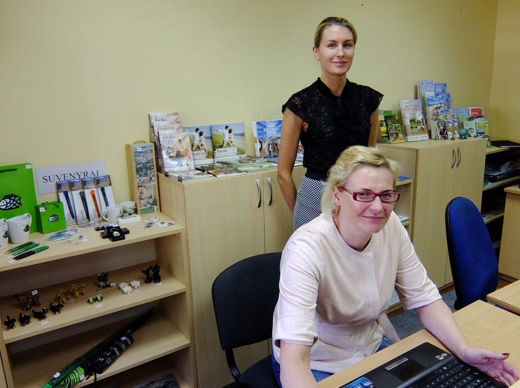 Šilutės turizmo informacijos centro direktorė Rasa Kmitienė (sėdi) ir vadybininkė Viktorija Paičiūtė į centrą užsukusiems suteikia ne tik informacijos, bet ir pasiūlo pirkti įvairių suvenyrų, leidinių apie Šilutės kraštą, lankstinukų, atvirukų, kalendoriukų ir kitko.