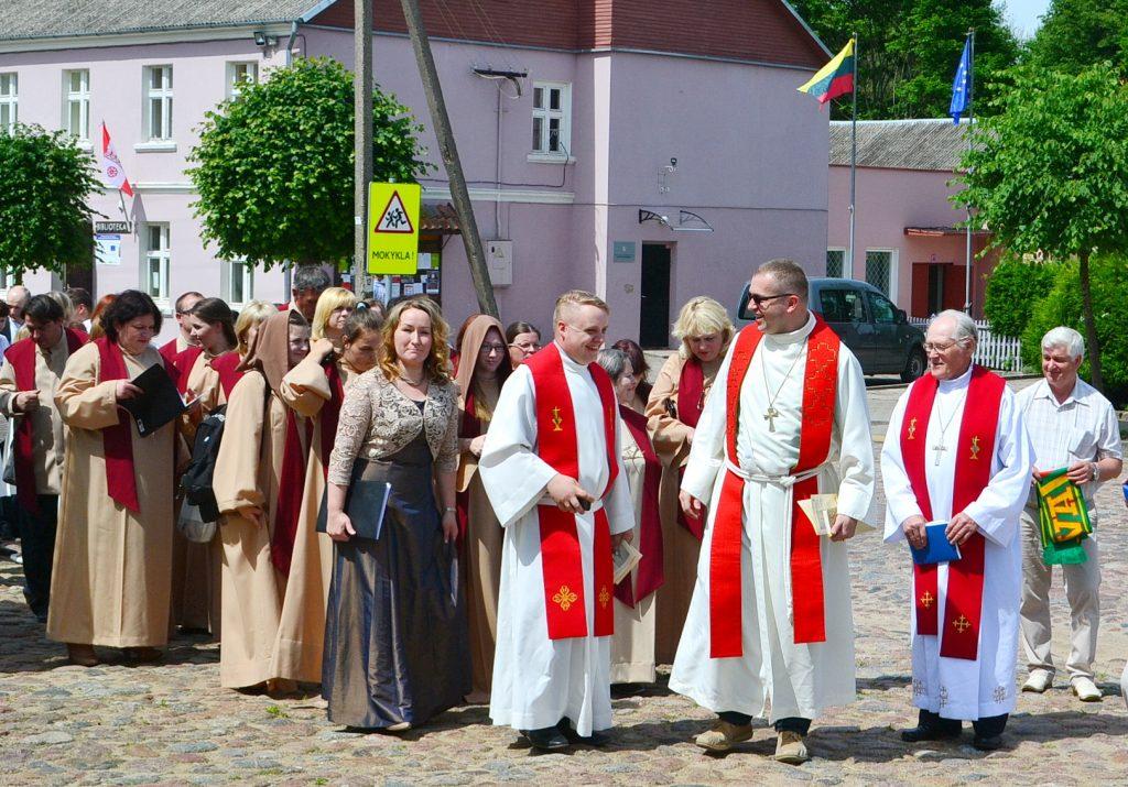 Per akmenimis grįsta Katyčių miestelio aikštę žygiavo evangeliškų bažnytinių chorų eisena. Jos priekyje – vyskupas Mindaugas Sabutis.