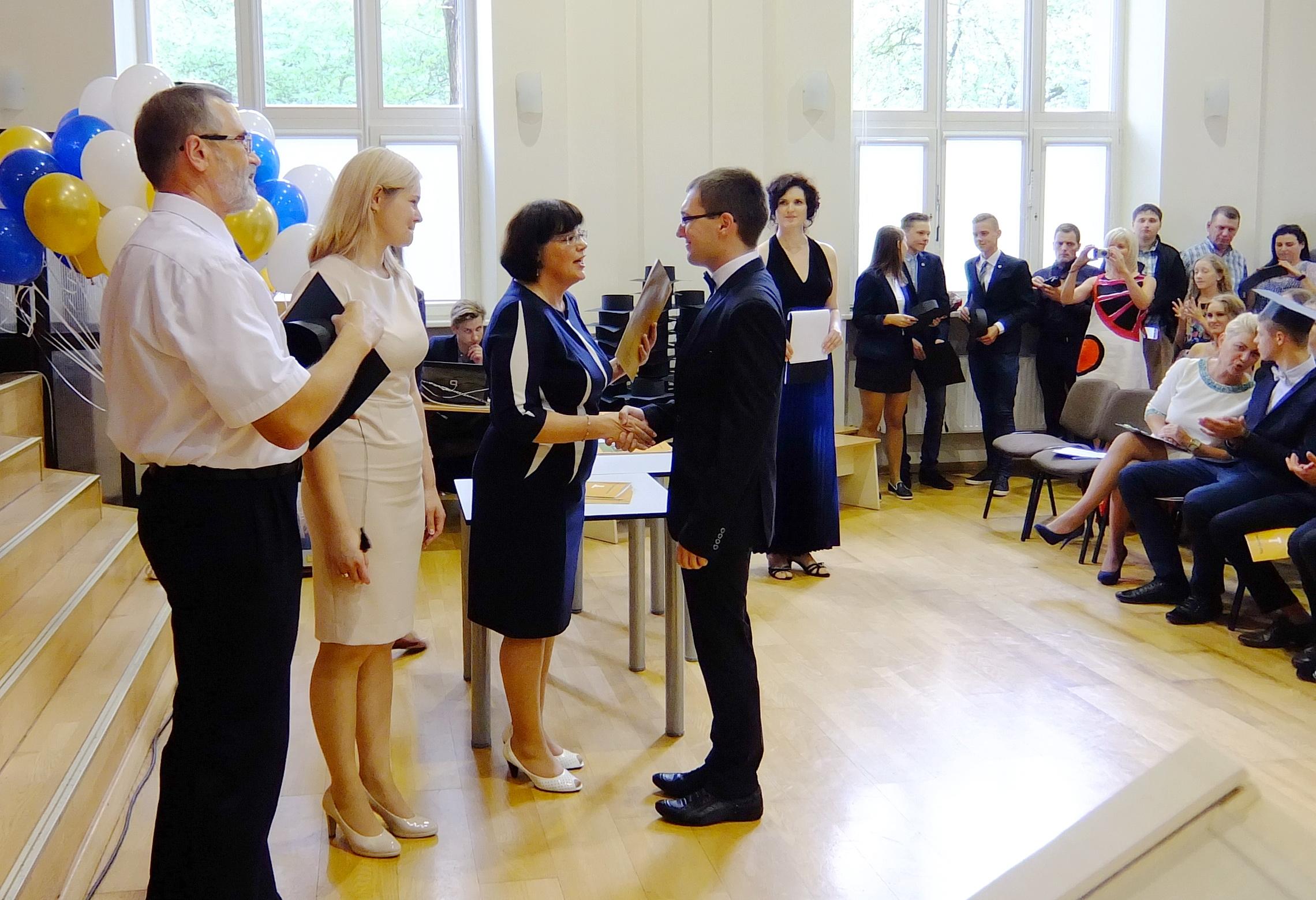 Abiturientui Martynui Šapalui įteikiamas brandos atestatas su pagyrimu.