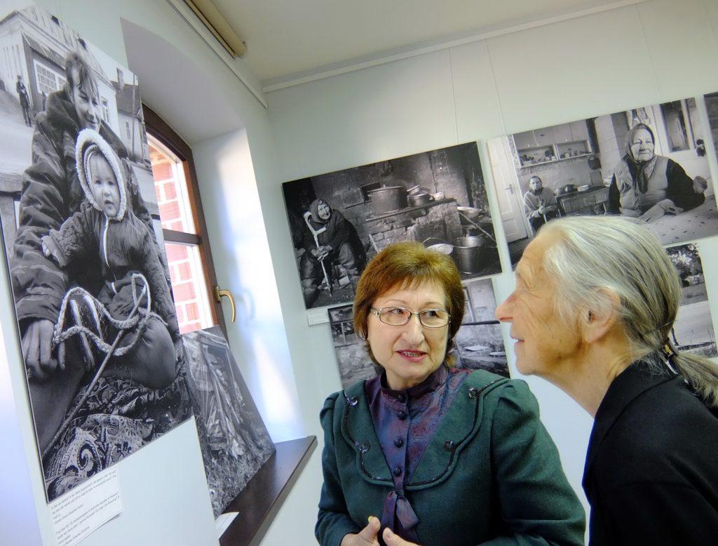 Giedrė Skipitienė ir Birutė Žemgulienė apžiūri fotografijų parodą.