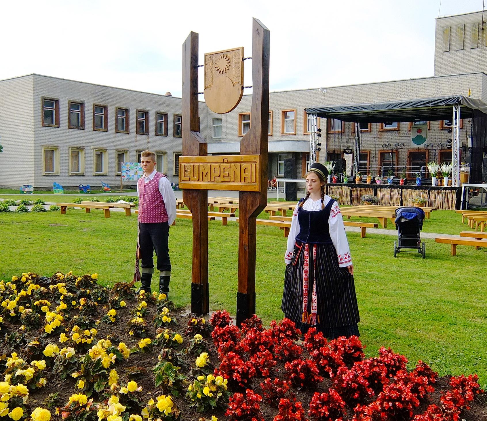Šalia paminklinio ženklo Lumpėnams per atidengimo iškilmes stovėjo tautiniais rūbais pasipuošusio jaunimo pora.