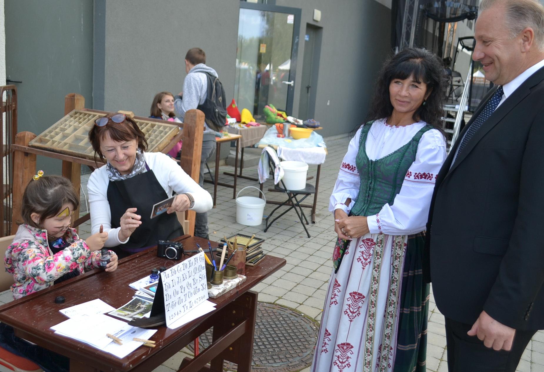 Meras Virginijus Komskis ir jo žmona Laima stebi, kaip anūkė Gerdutė senoviniu rašikliu užrašo atvirlaiškį.