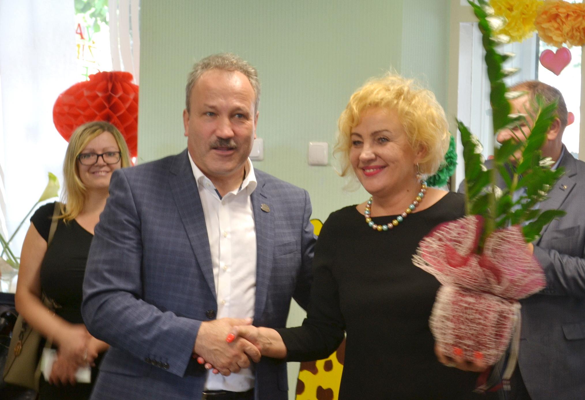 """Meras Vytautas Laurinaitis Vaikų užimtumo centro, įkūrusio Vaikų dienos centrą, direktorei Irenai Domarkienei padovanojo gėlę – vadinamąjį """"pinigų medį""""."""