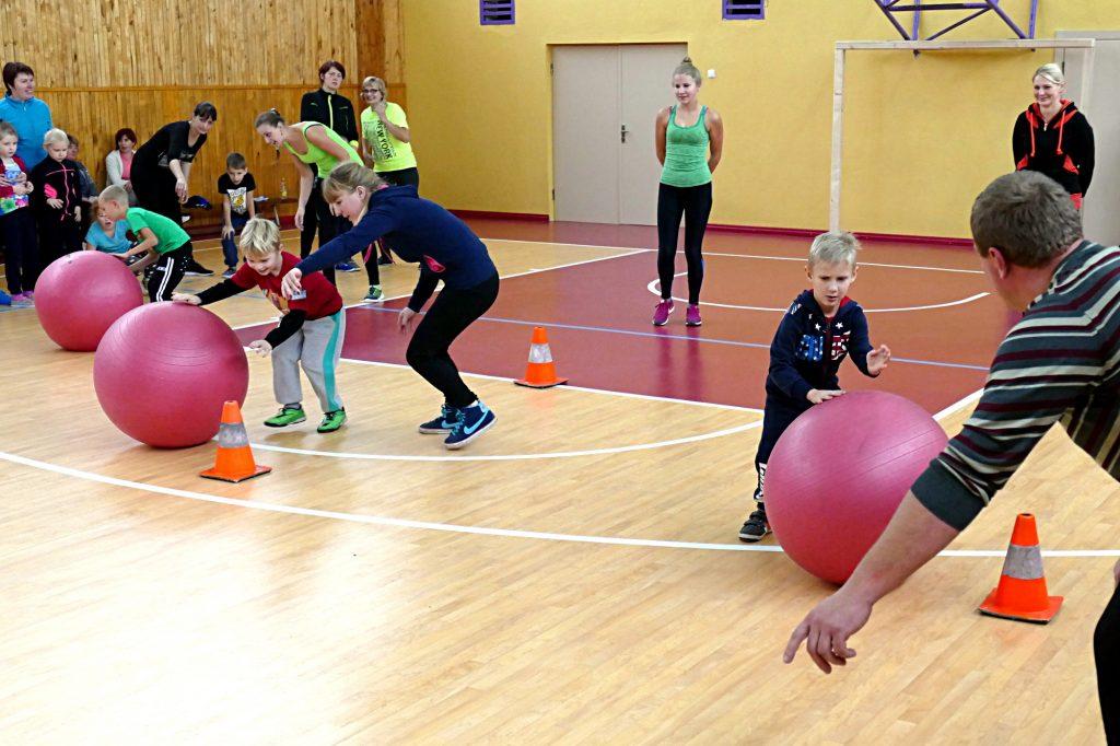 Kad mažieji nesuklystų, kokia tvarka pro kliūtis reikia ridenti kamuolius, jiems talkino vyresnieji šeimų nariai.